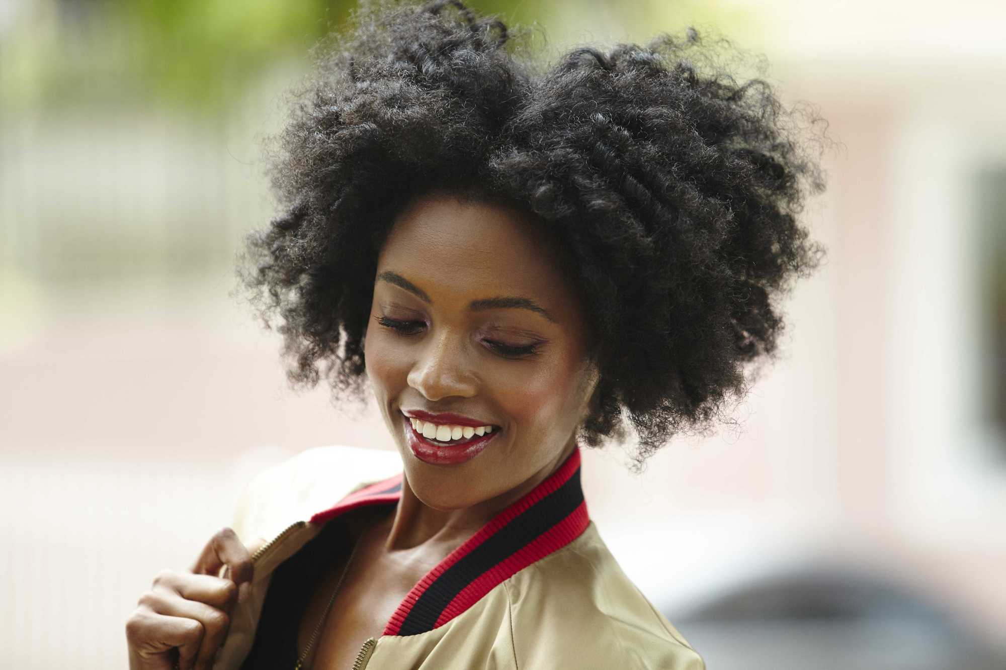 Easy natural hairstyles: Close up shot of woman with a twist out natural hair, wearing a bomber jacket and posing outside.