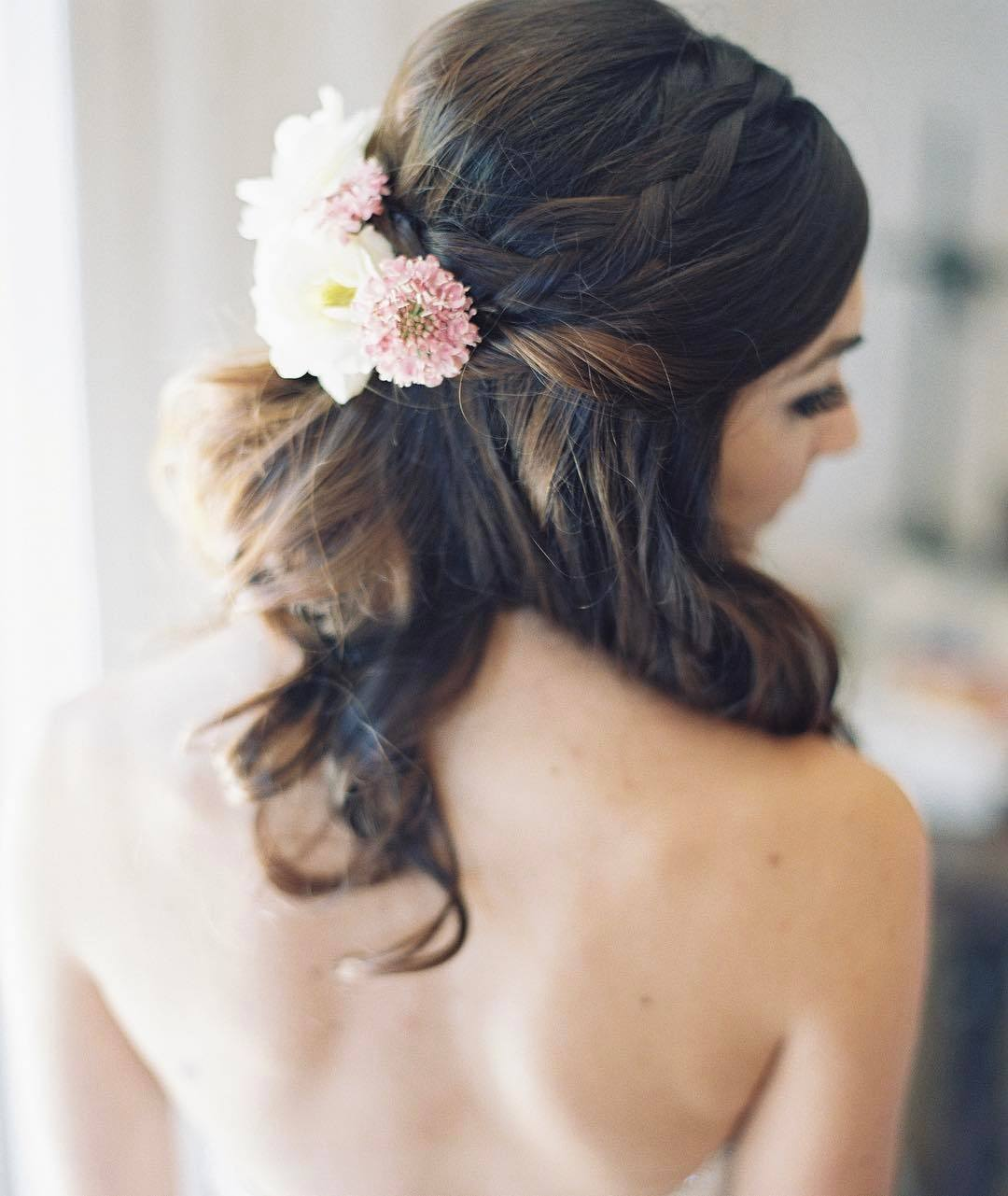 Wedding hairstyles: Woman medium-length dark brown hair styled into a wavy half-up, half-up braids with flowers