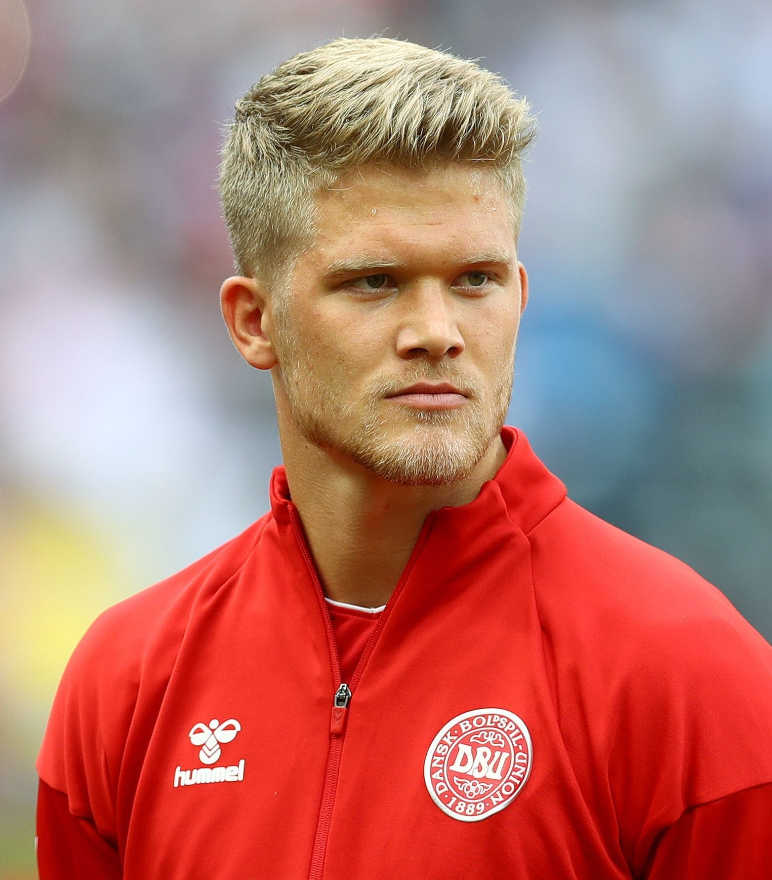footballer hairstyles: andreas cornelius with short blonde hair with side parting swept back teamed with a blonde beard in denmark football shirt