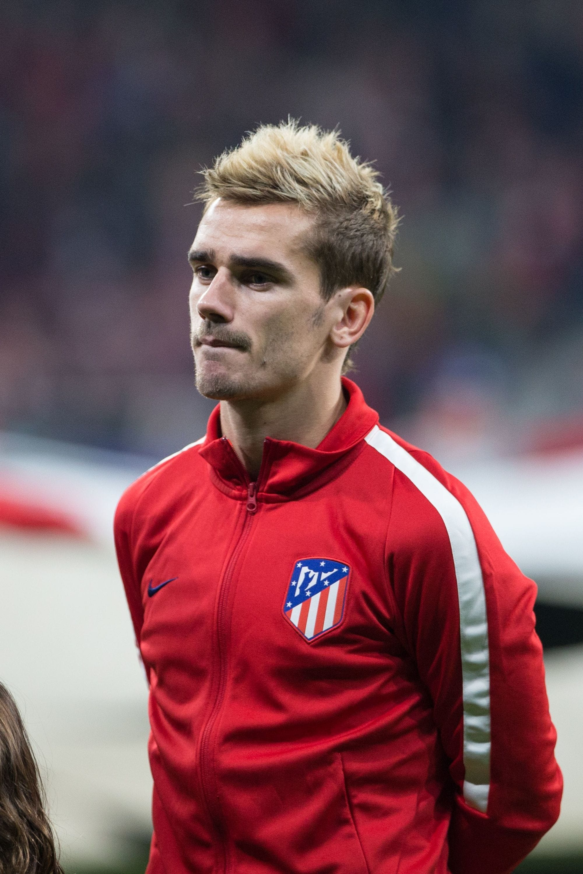 french footballer Antoine Griezmann with blonde spiky hair standing on the pitch