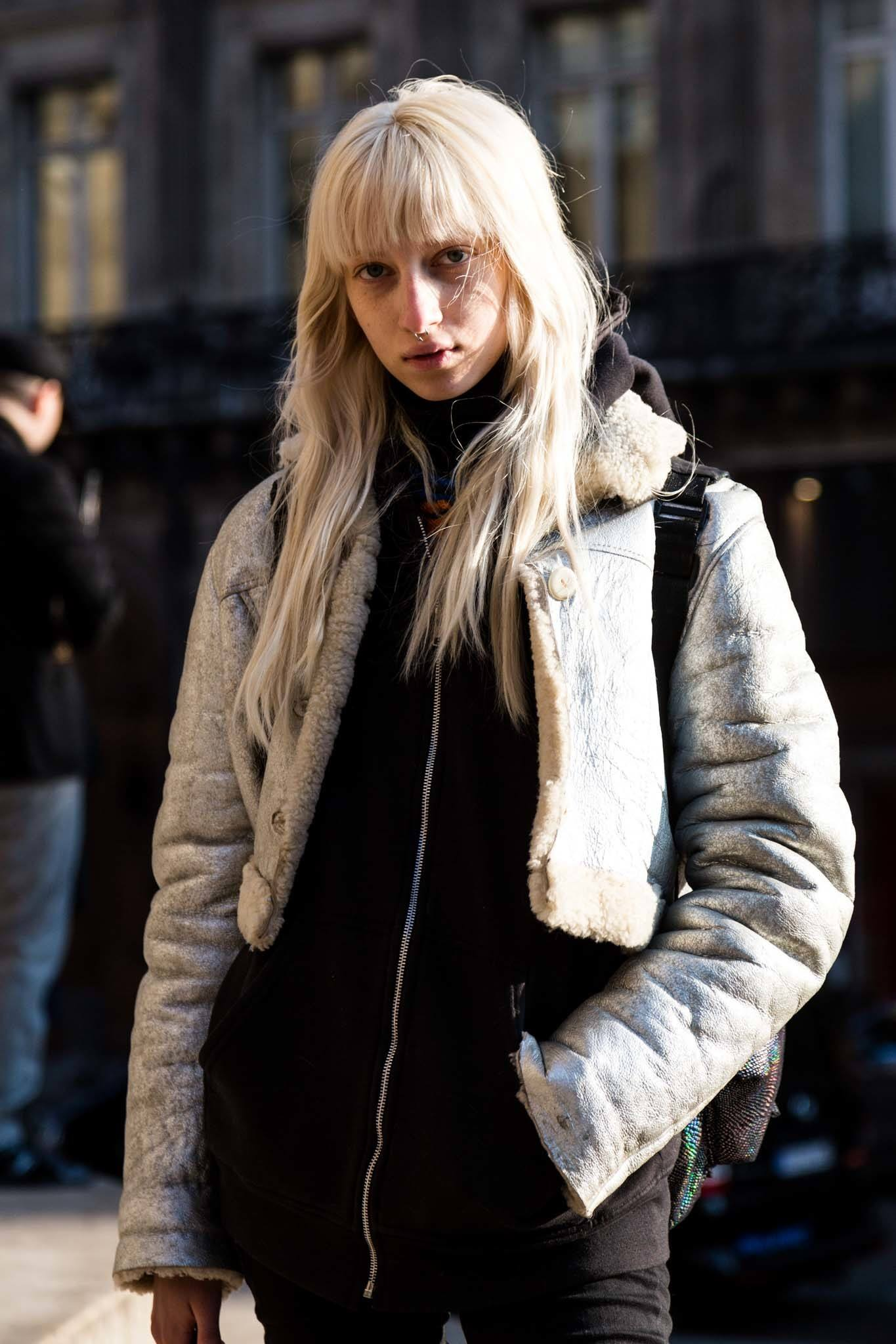 Shot of street style model with long ashy blonde hair and full bangs, wearing winter clothing and posing outside