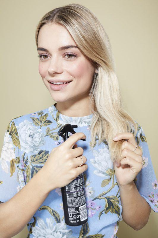Beach waves hair: Blonde model spraying her medium length hair with a heat protect spray wearing a floral light blue summer top.