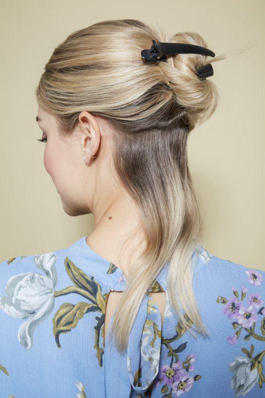 Beach waves hair: Blonde model sectioning her medium length hair wearing a floral light blue summer top.