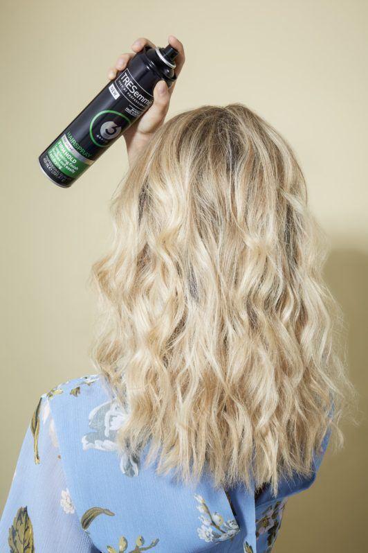 Beach waves hair: Blonde model spraying hairspray on her curly hair wearing a floral light blue summer top.
