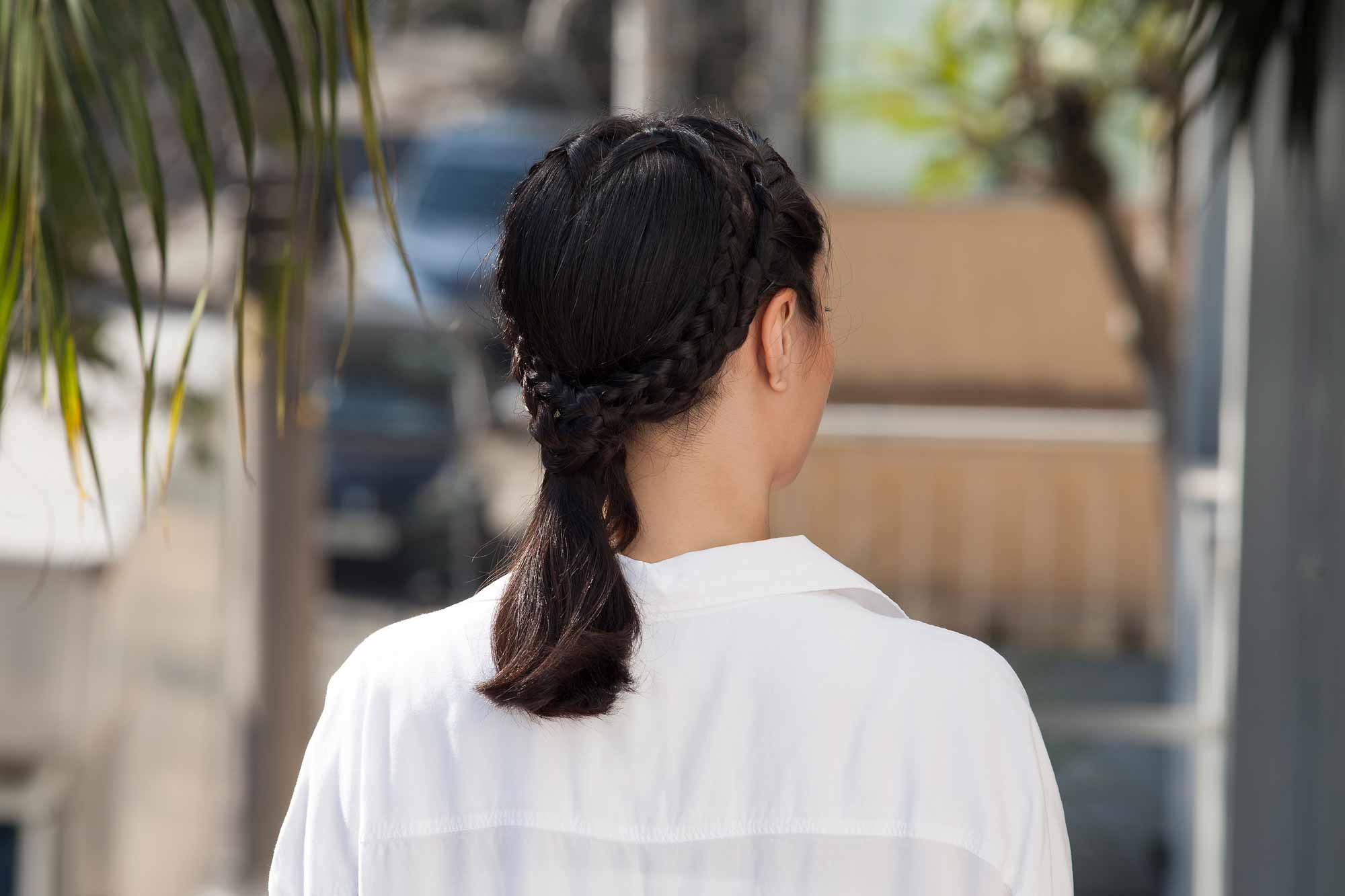 close up shot of model with heart braid ponytail hairstyle, wearing white blouse and posing outside