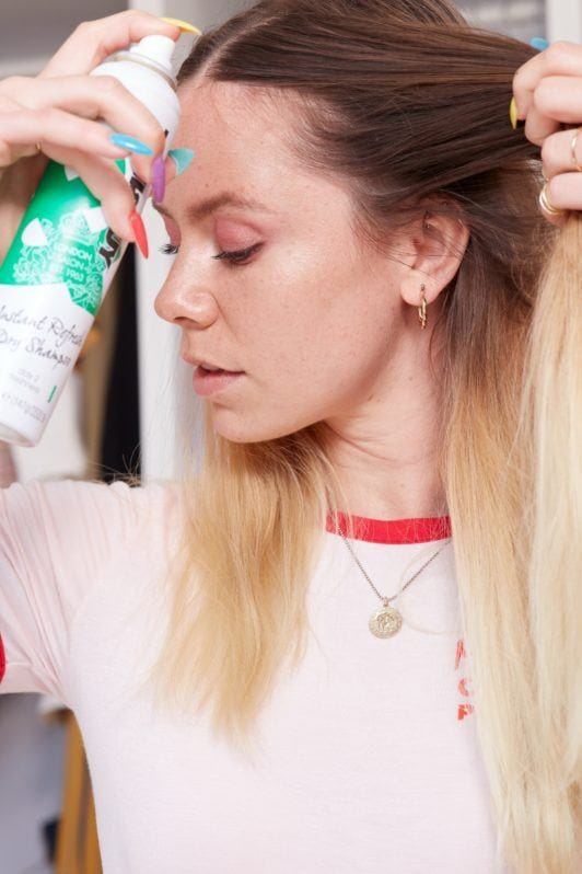 heart braid tutorial: close up shot of woman spraying dry shampoo into her roots, wearing white top and necklace, posing in a bedroom
