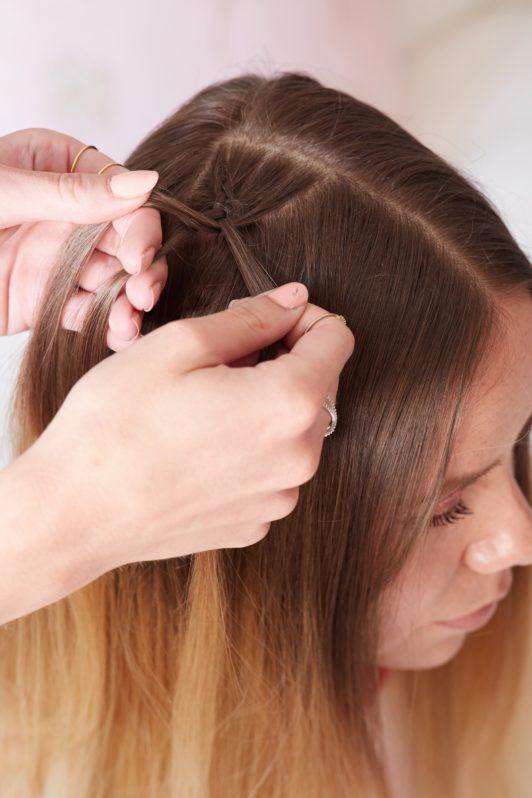 heart braid tutorial: close up shot of a model getting a dutch braid done by her friend