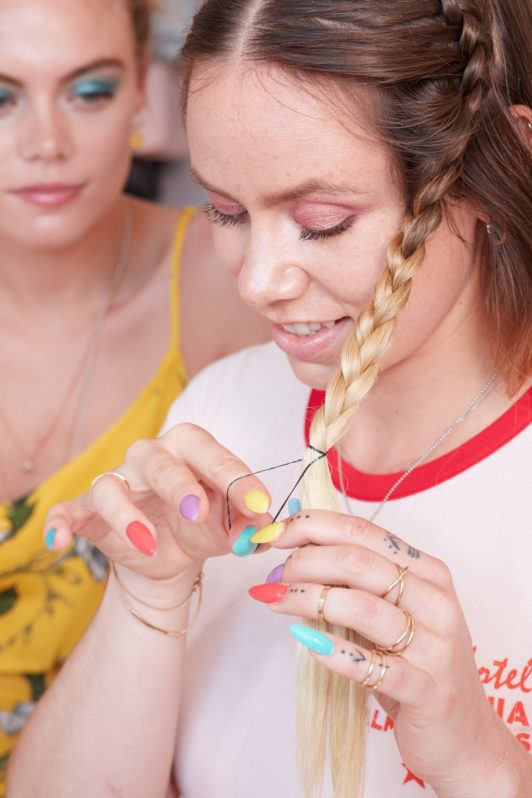 heart braid tutorial: close up shot of a model finishing off her standard braid with an elastic, wearing white top and posing in a bedroom