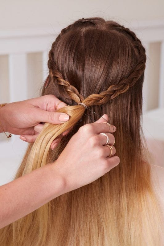heart braid tutorial: close up shot of model with a heart braided hairstyle, which is being secured by an elastic band