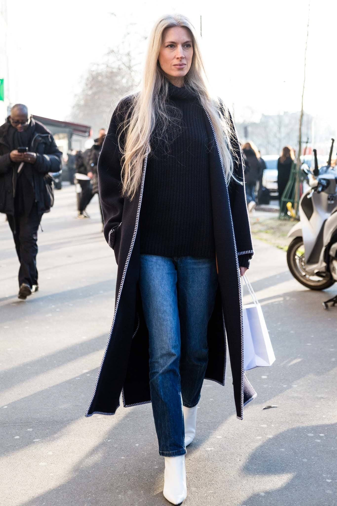 Ash blonde hair: Shot of woman on the street with long ashy blonde hair, wearing a long line black coat with jeans and white trainers outside