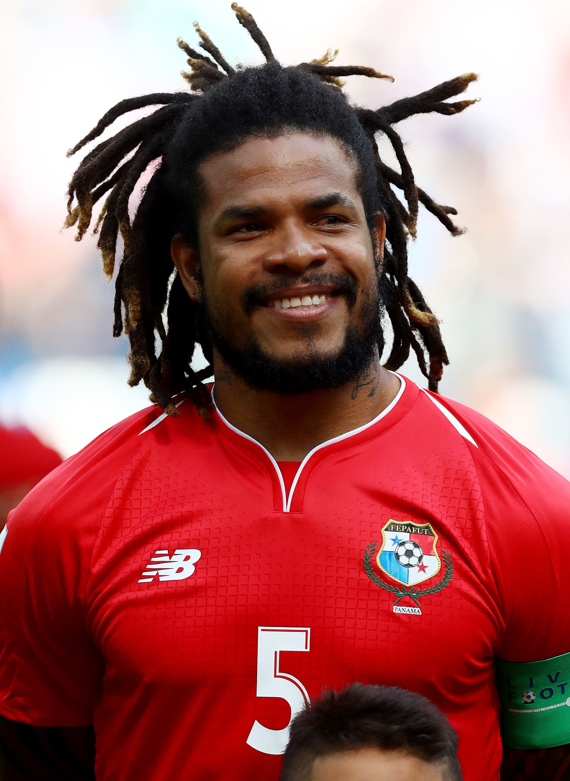 footballer hairstyles: roman torres with brown long locs pulled away from the face