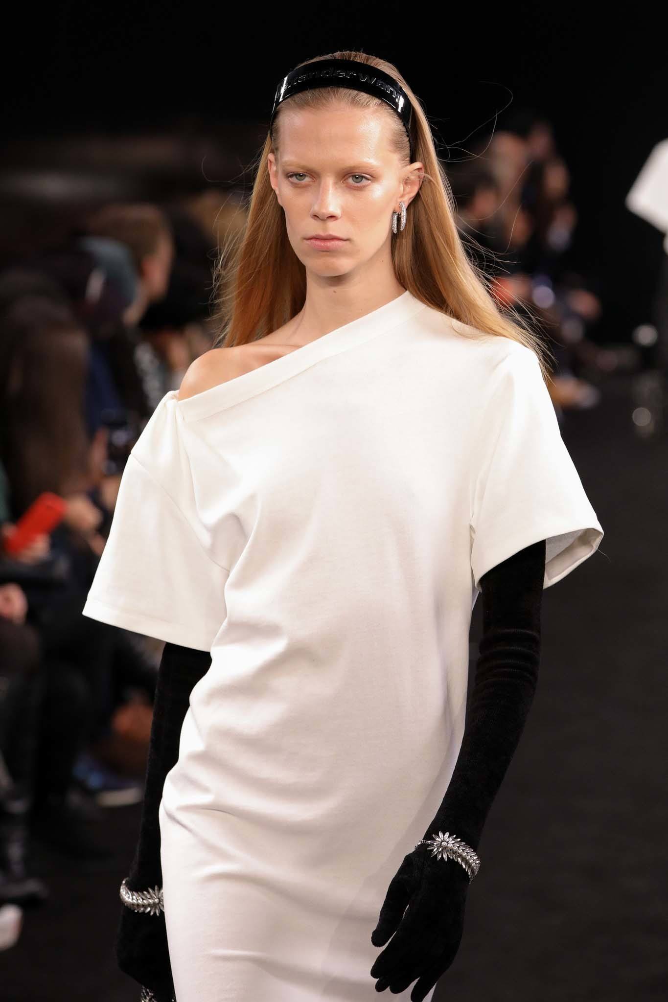 Headband and bandana hairstyles: Model with long dark blonde straight hair with a black patent headband wearing a white off the shoulder dress ad long black gloves on Alexander Wang SS19 runway.