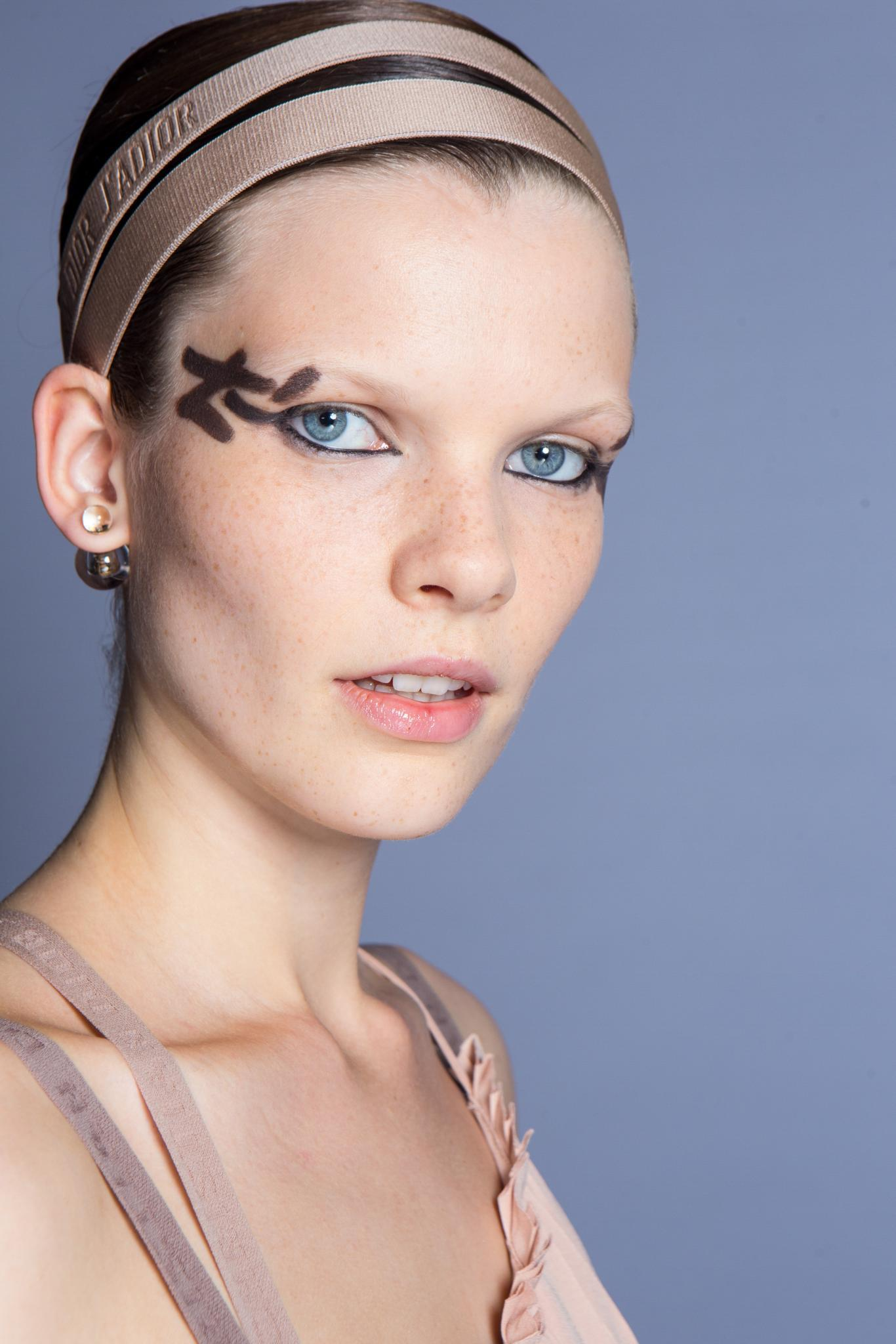 Headband and bandana hairstyles: Model at Dior SS19 with hair in a sleek bun updo wearing a double pink headband and bold eye makeup.