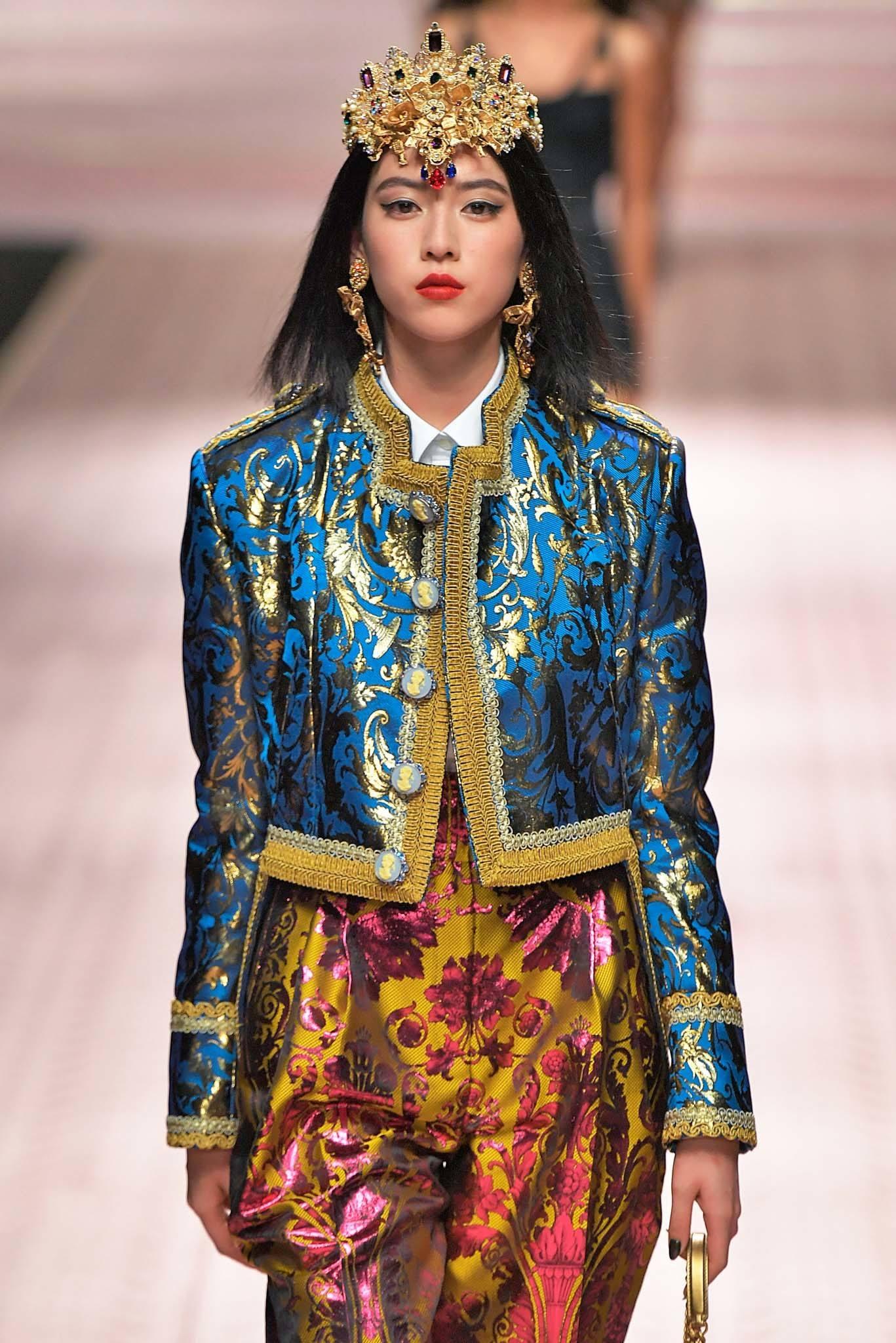 Headband and bandana hairstyles: Woman on Dolce and Gabbana SS19 runway with straight dark brown medium hair wearing a gold tiara OTT headband.