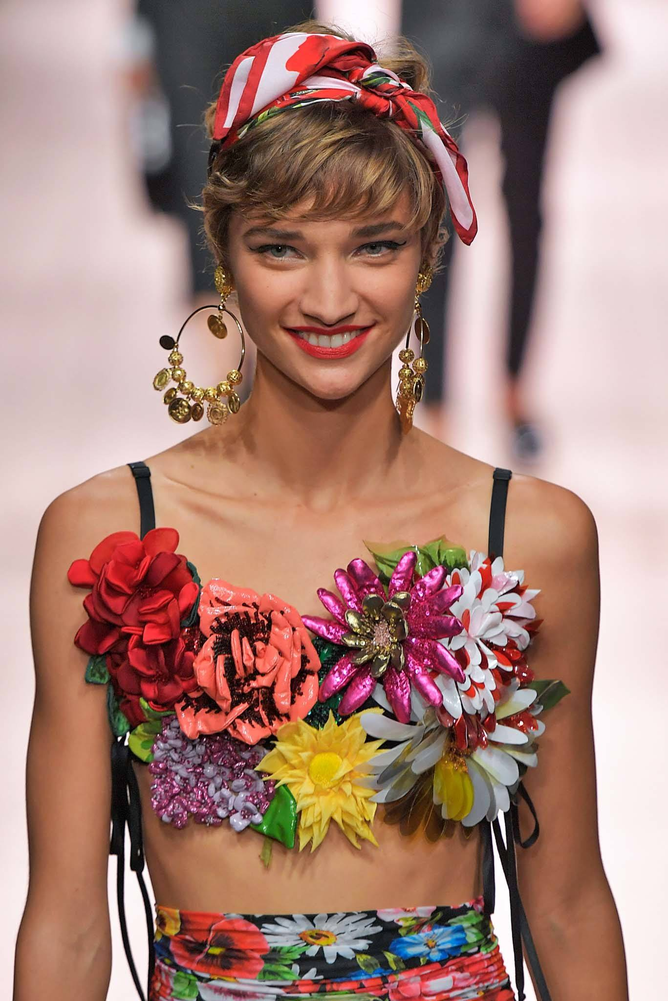 Headband and bandana hairstyles: Model at Dolce and Gabbana SS19 show with light brown pixie cut wearing a red stripped head scarf and floral summer outfit.