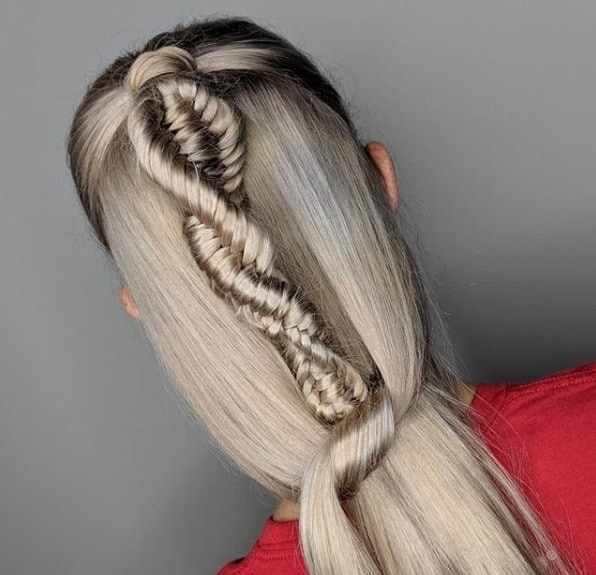 Back view of a woman with ash blonde/grey long straight hair in a half-up half-down DNA braid.
