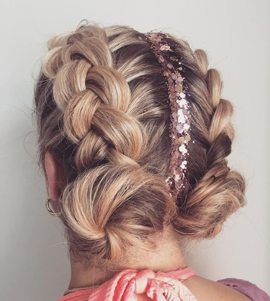Back view of a blonde with two Dutch braided space buns with copper bronze glitter roots