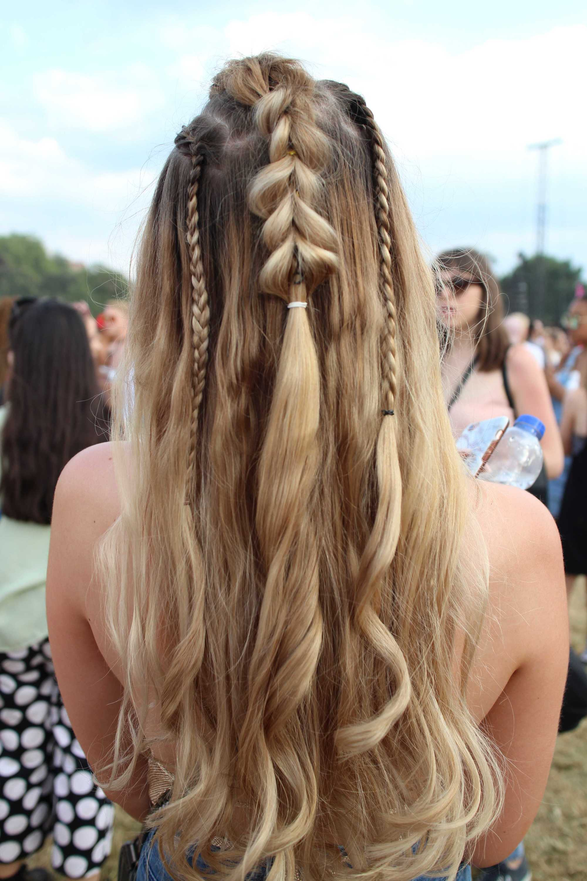 Back view of a woman at Lovebox festival with curled long blonde hair in a half-up pull through braid style with hidden braids.