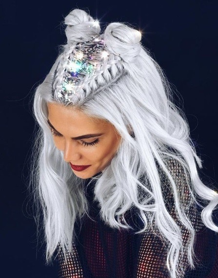 Woman with icy silver grey curly long hair in braided space buns with silver glitter roots