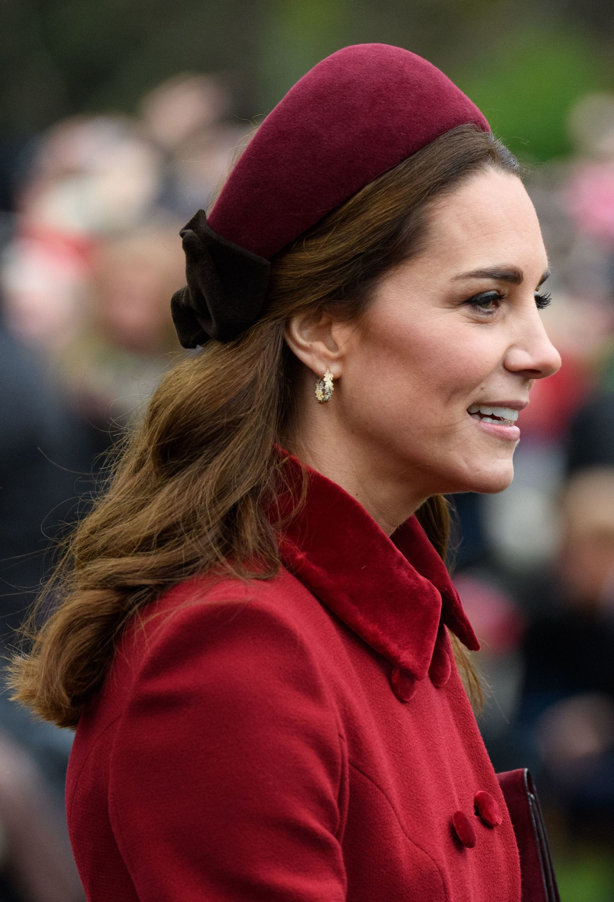 Headband and bandana hairstyles: Kate Middleton with medium length wavy brown hair wearing a burgundy red headband and matching jacket.