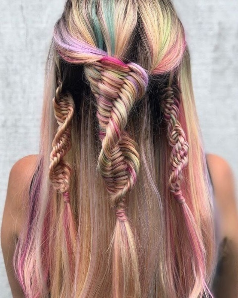 Back view of a woman with long, straight, multicoloured pastel hair in multiple half-up DNA braids.