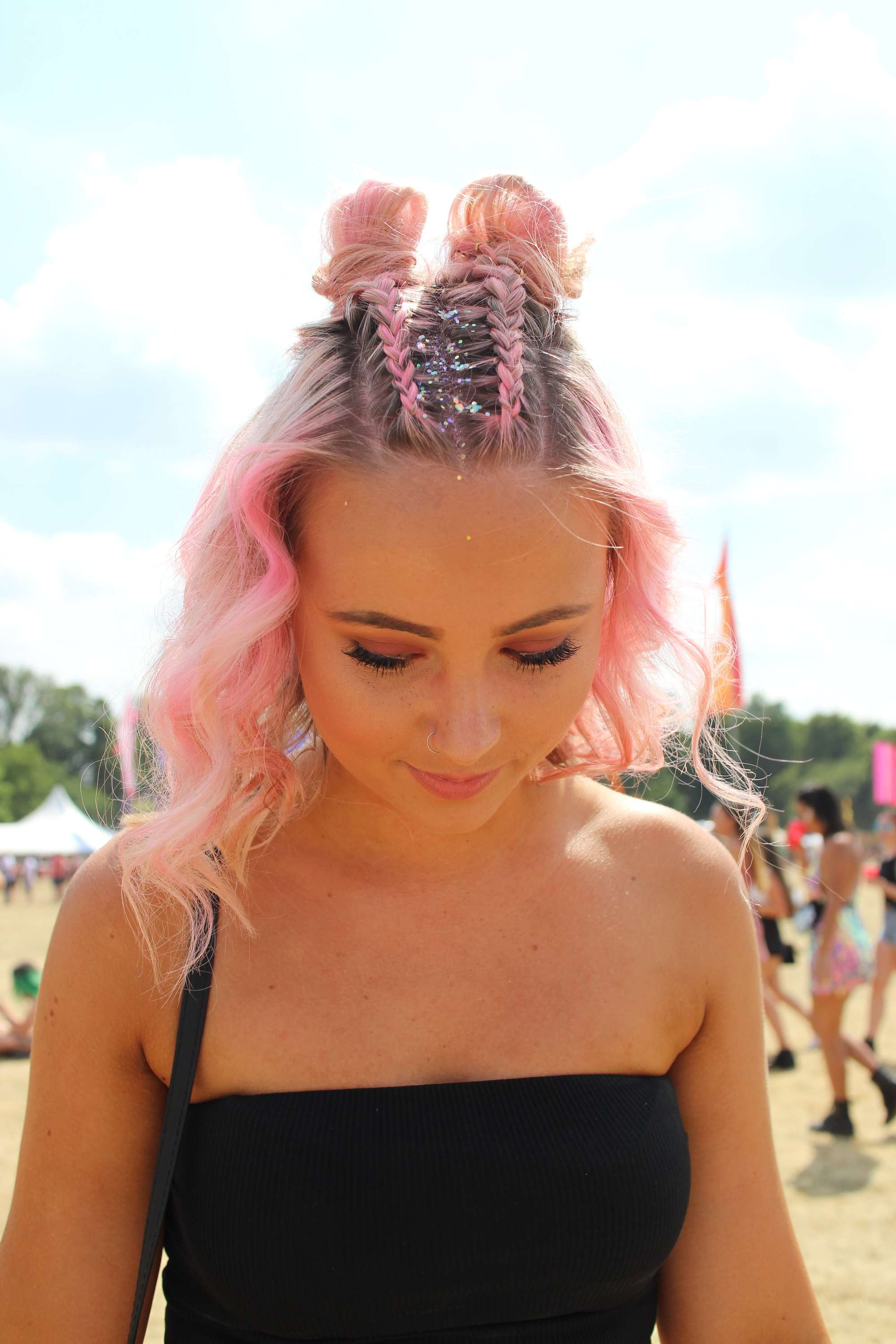 Photo of a woman with candyfloss pink curly hair in braided space buns with holographic glitter roots