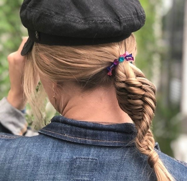 Close up shot of a woman with light brown hair in a DNA braided ponytail wearing a black baker boy hat.