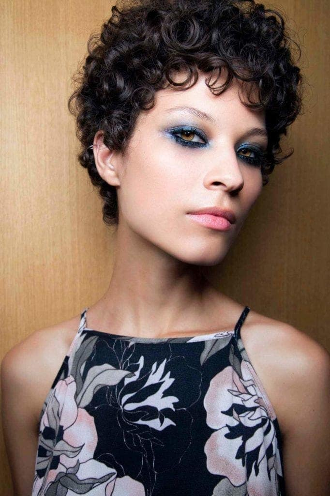 Prom hairstyles: Woman with curly brown short hair wearing a pattern dress.