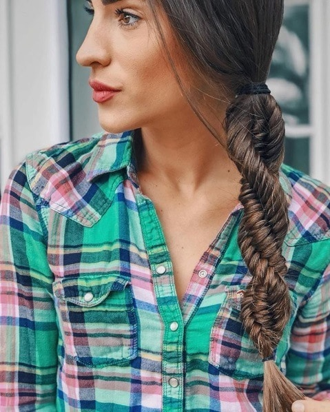 Close up shot of a woman with long brunette hair in a side braided DNA braid, wearing a green and pink plaid shirt.