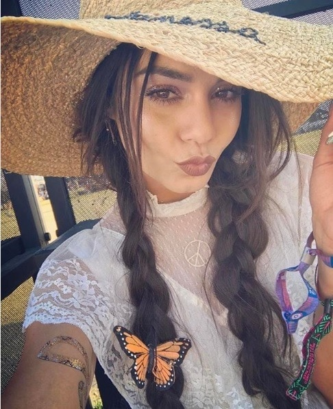 Vanessa Hudgens Coachella selfie with long brunette hair in pigtail plaits with butterfly clips and a big floppy straw hat.