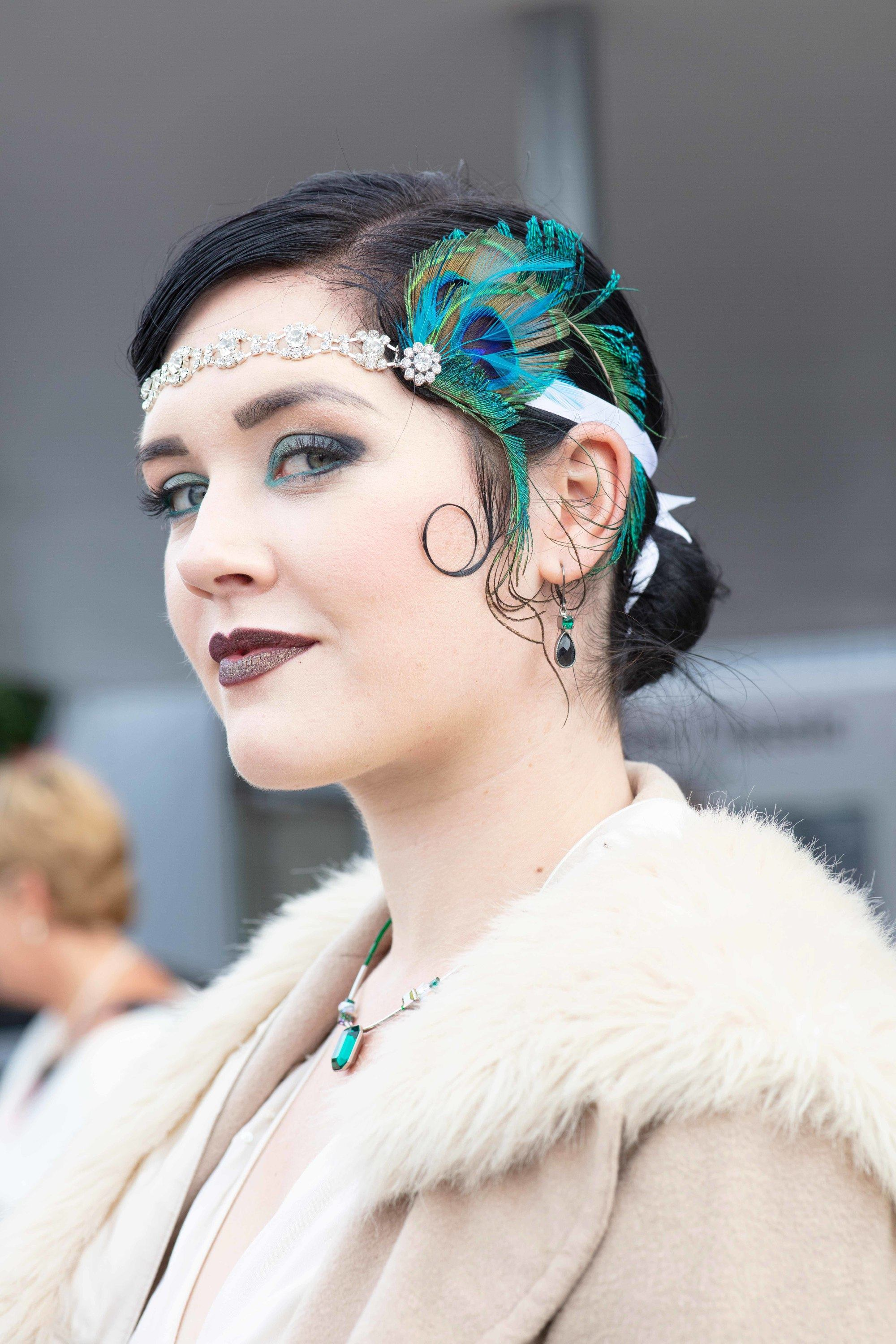 Vintage updo hairstyles: Woman with dark brown hair in a vintage low bun with kiss curl and peacock feather