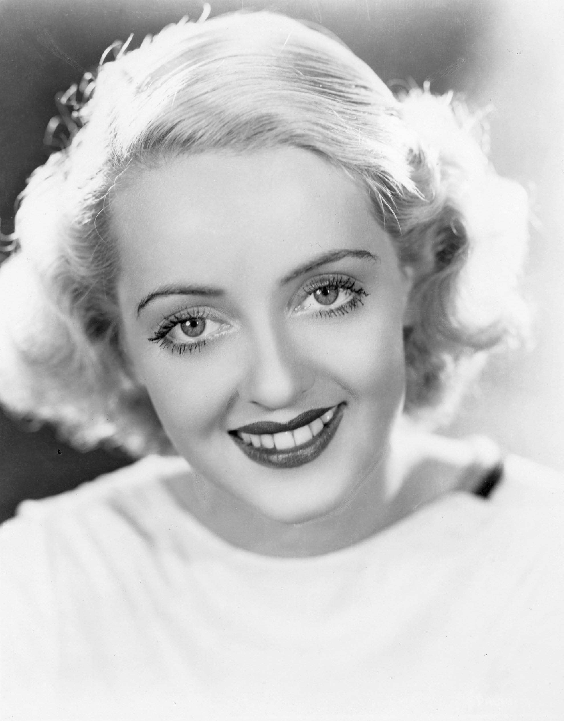 1930s hairstyles: close up of bette davis with bob length bleach blonde wavy vintage hair in black and white image