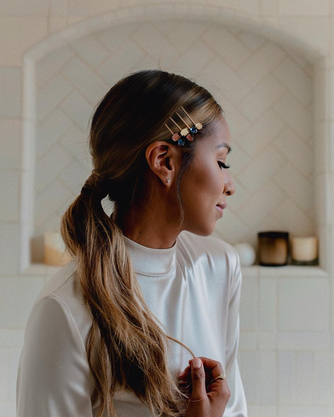 Woman with long dark brown hair with caramel highlights styled into a low ponytail, wearing hair slides and posing in a bedroom setting