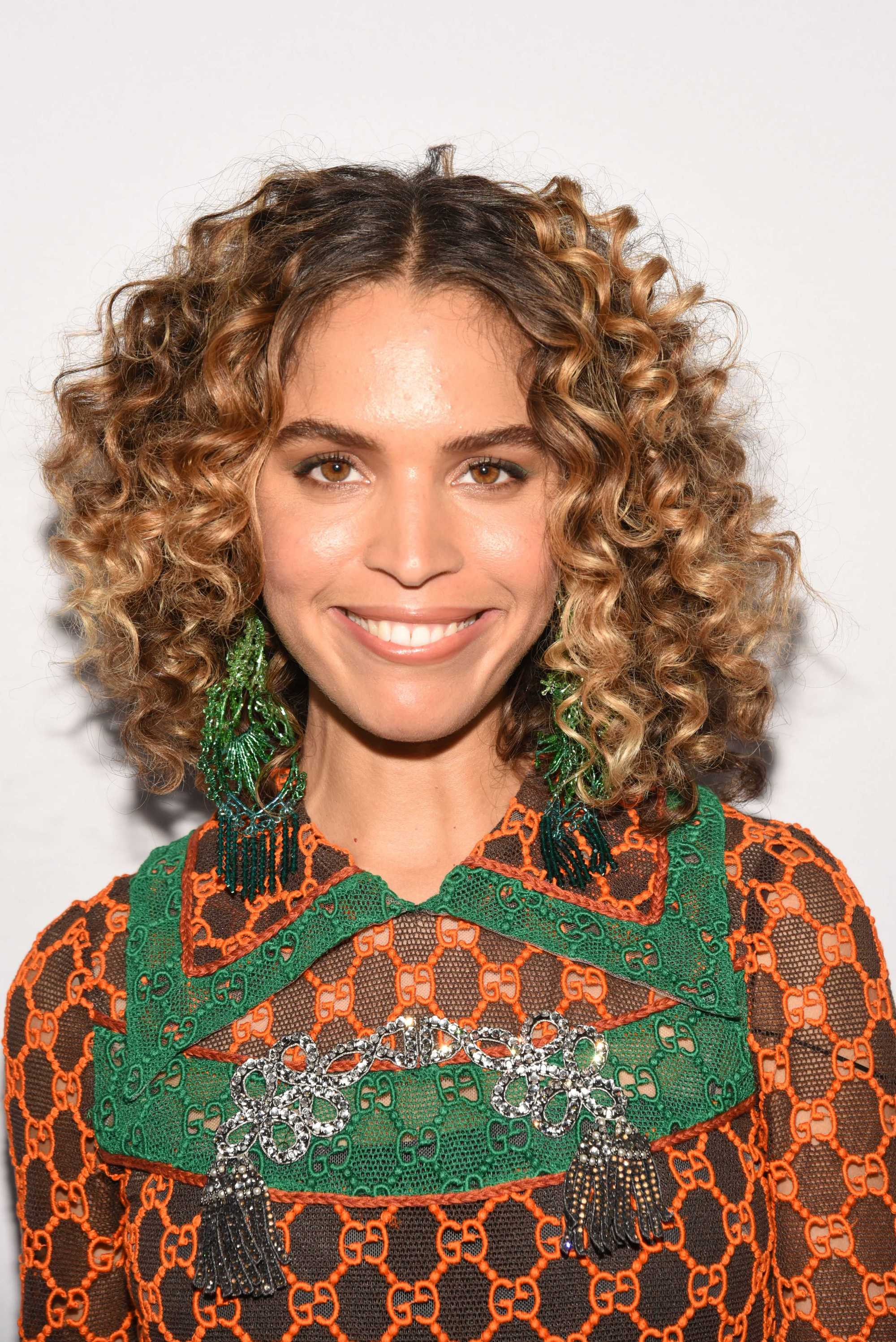 Cleo Wade with long naturally curly bob with caramel and blonde highlights in it, wearing a patterned top on the red carpet
