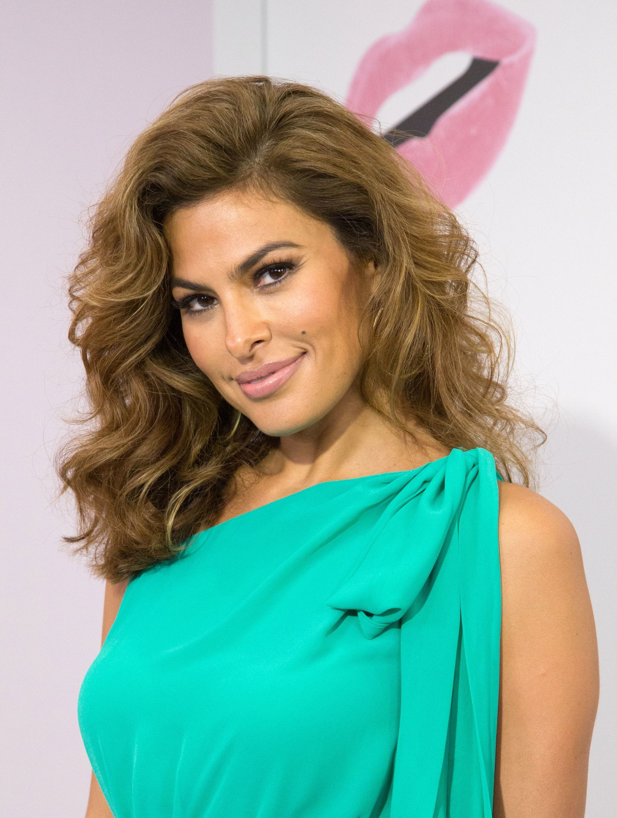 Eva Mendes with medium-length textured caramel waves, wearing green on the red carpet and posing