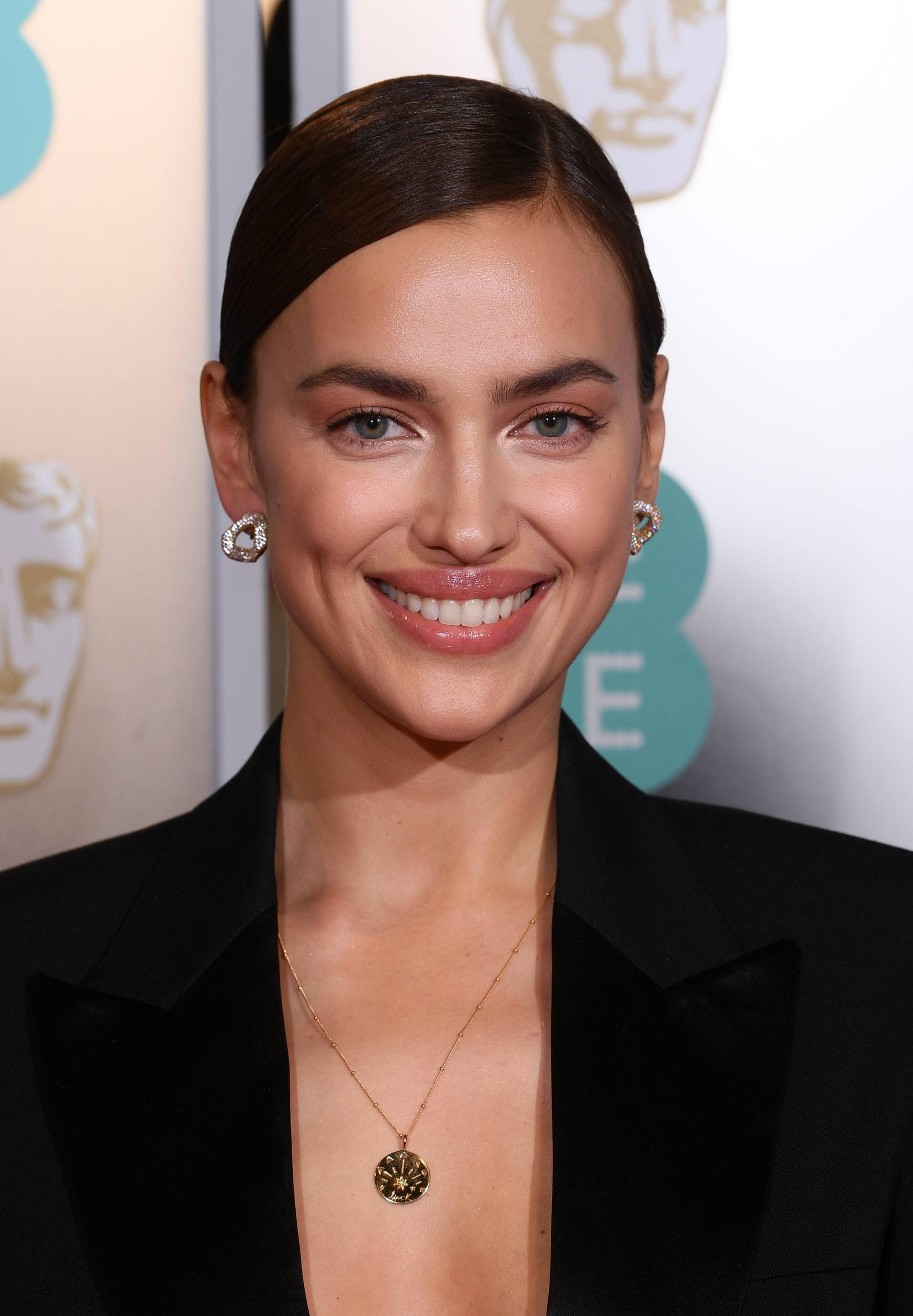 Red carpet hairstyles: Irina Shayk with brown hair styled in side parted smooth bun updo wearing a black smart jacket.