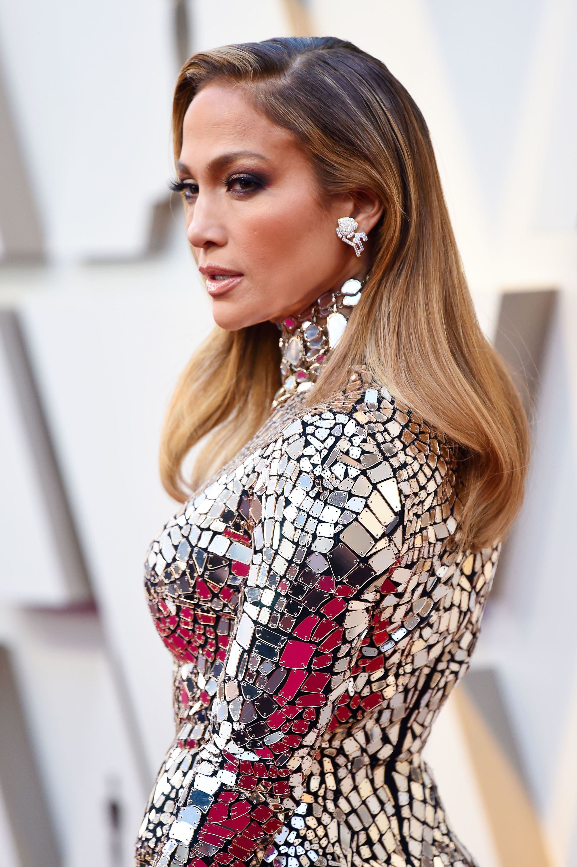 Jennifer Lopez on the red carpet with long, sleek dark to light caramel hair, wearing glittery outfit on the red carpet