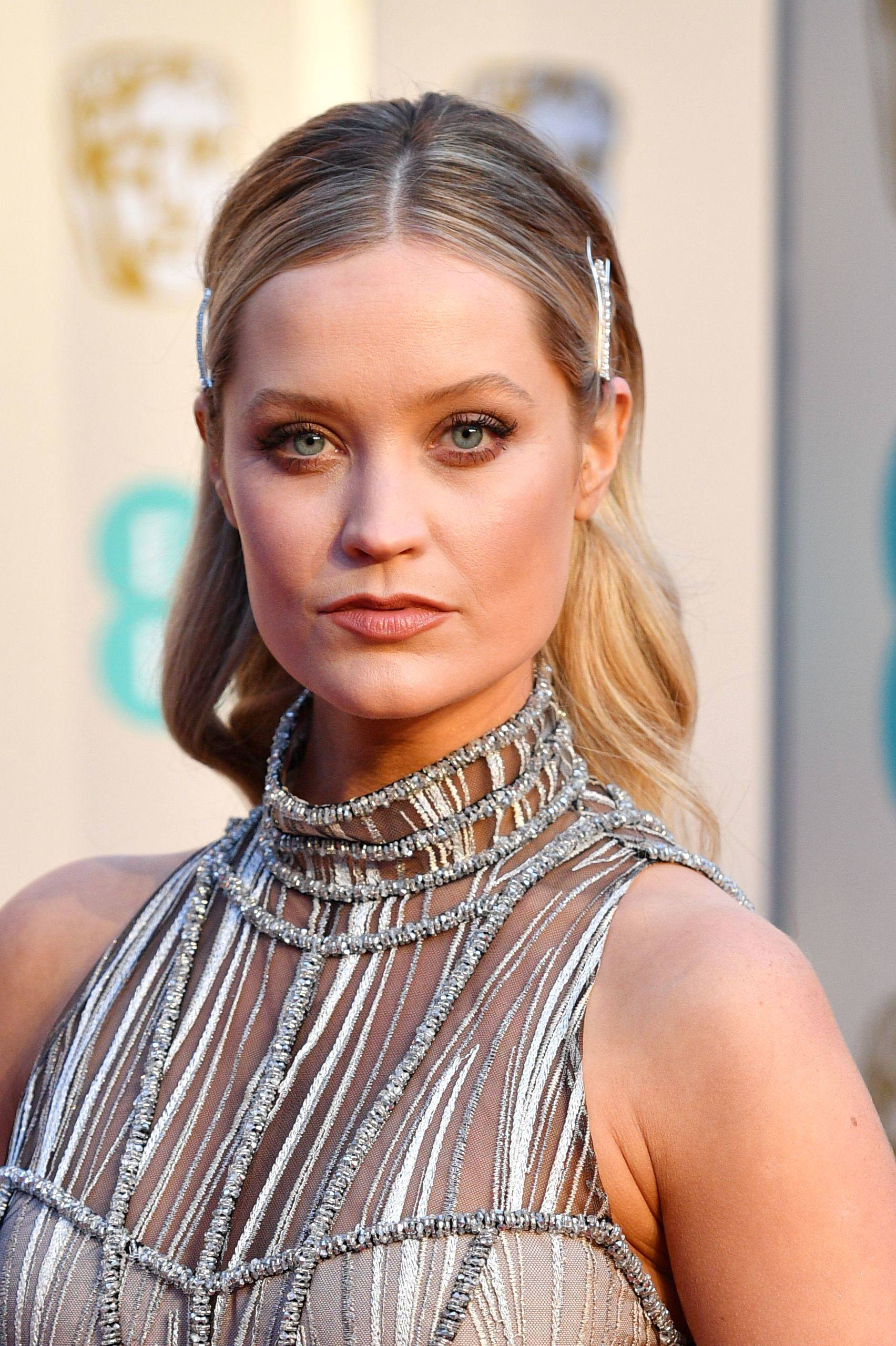 Red carpet hairstyles: Laura Whitmore with long wavy blonde hair pinned back with hair slides at the Baftas.