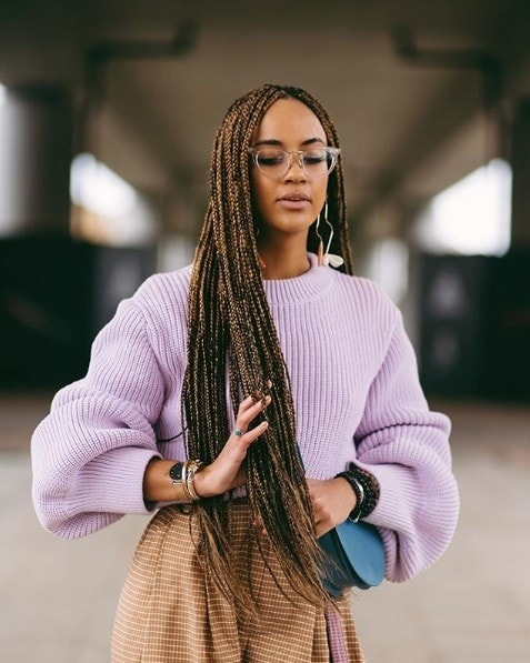 Long box braids: Woman with extra long brunette box braids, wearing a lilac jumper and glasses