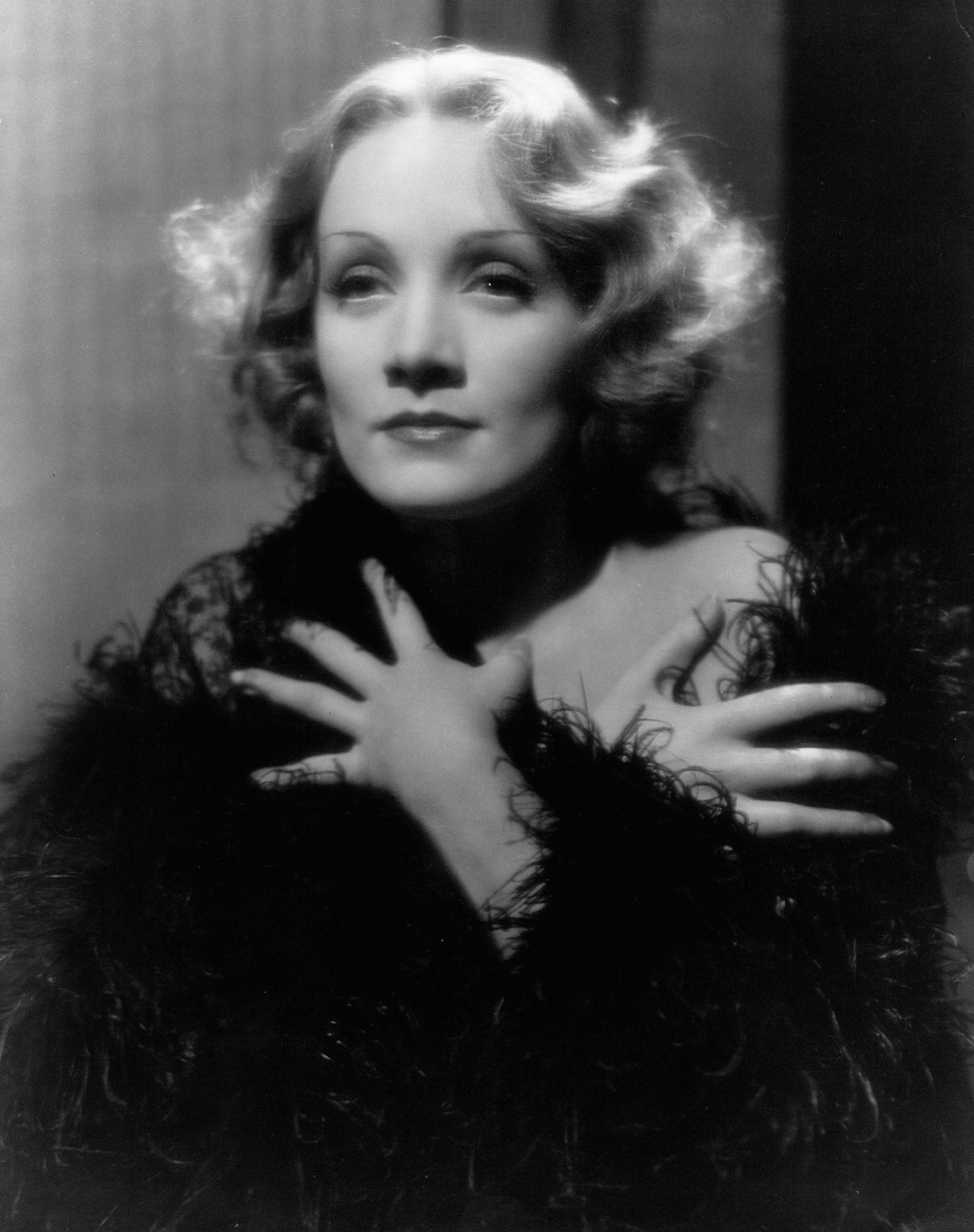 1930s hairstyles: Marlene Dietrich black and white promo photo with blonde fluffy vintage waves on bob length hair