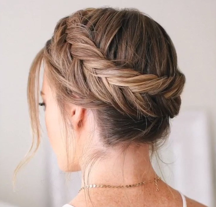 Crown hair: Close up shot of a woman with dirty blonde hair styled into a Dutch fishtail crown braid