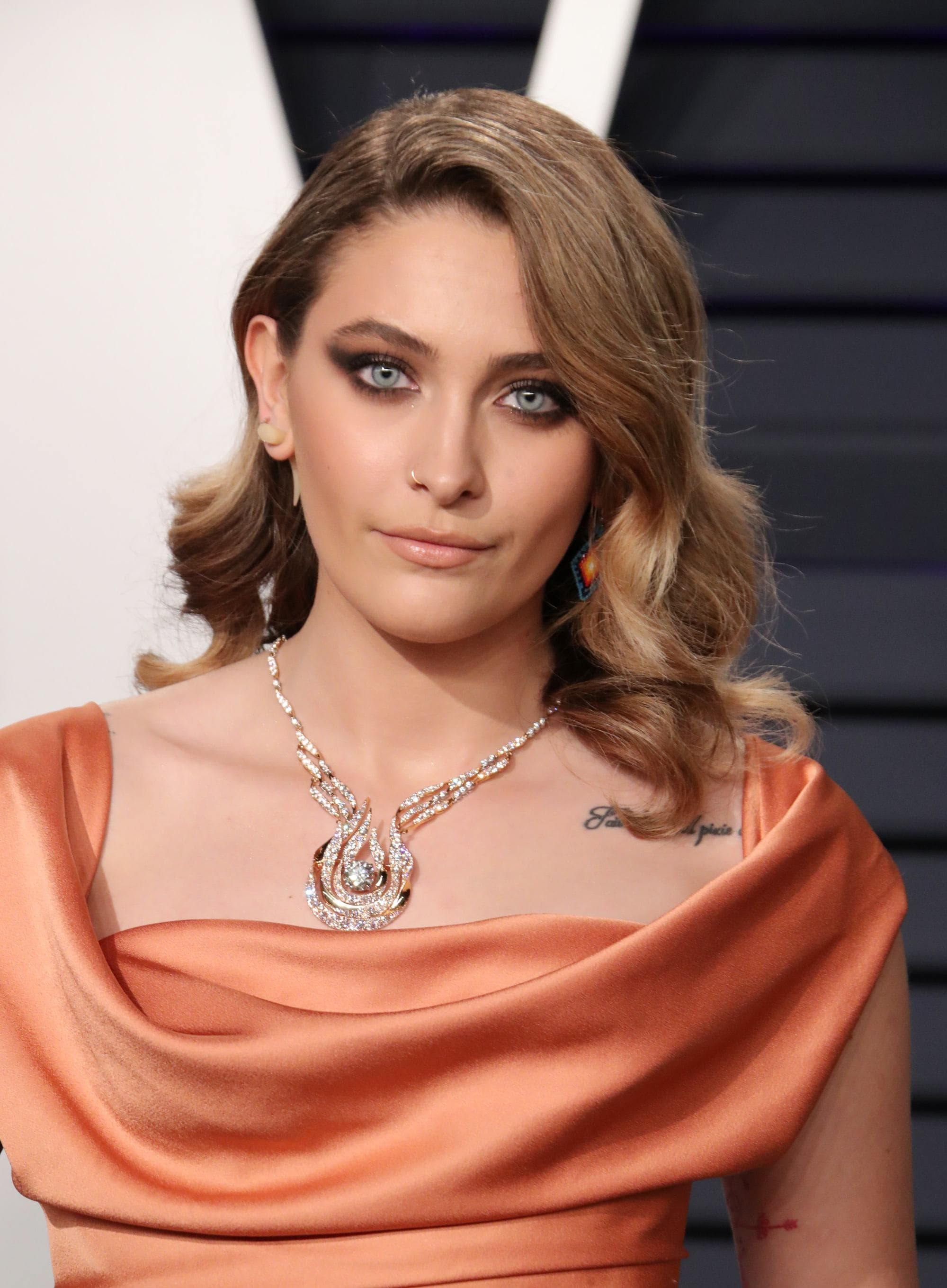 Paris Jackson on the red carpet with tawny caramel hair swept to the side and styled into retro curls, wearing orange top