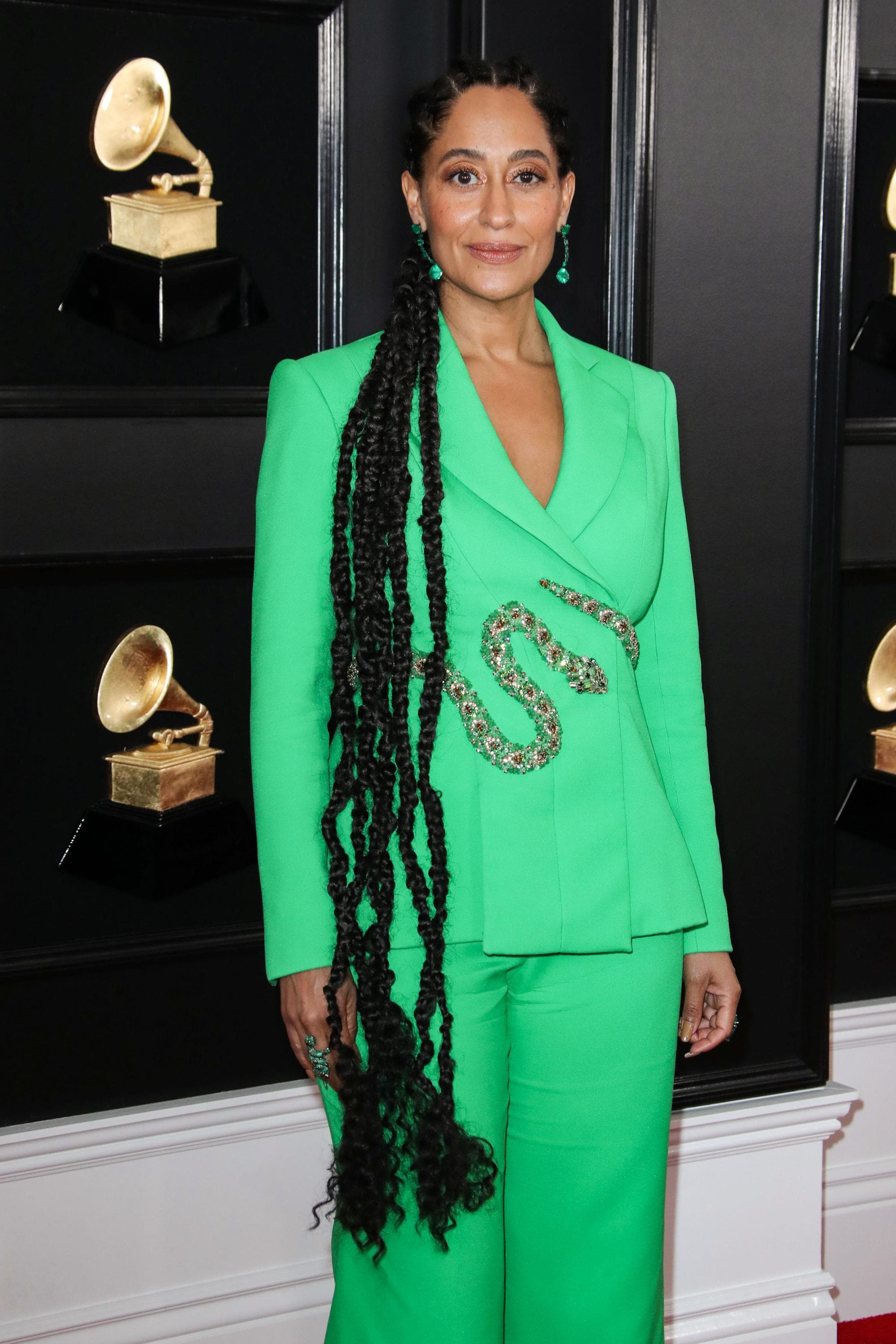Red carpet hairstyles: Tracee Ellis Ross with very long braided hair wearing a green suit and snake belt at the Grammy Awards 2019 red carpet.