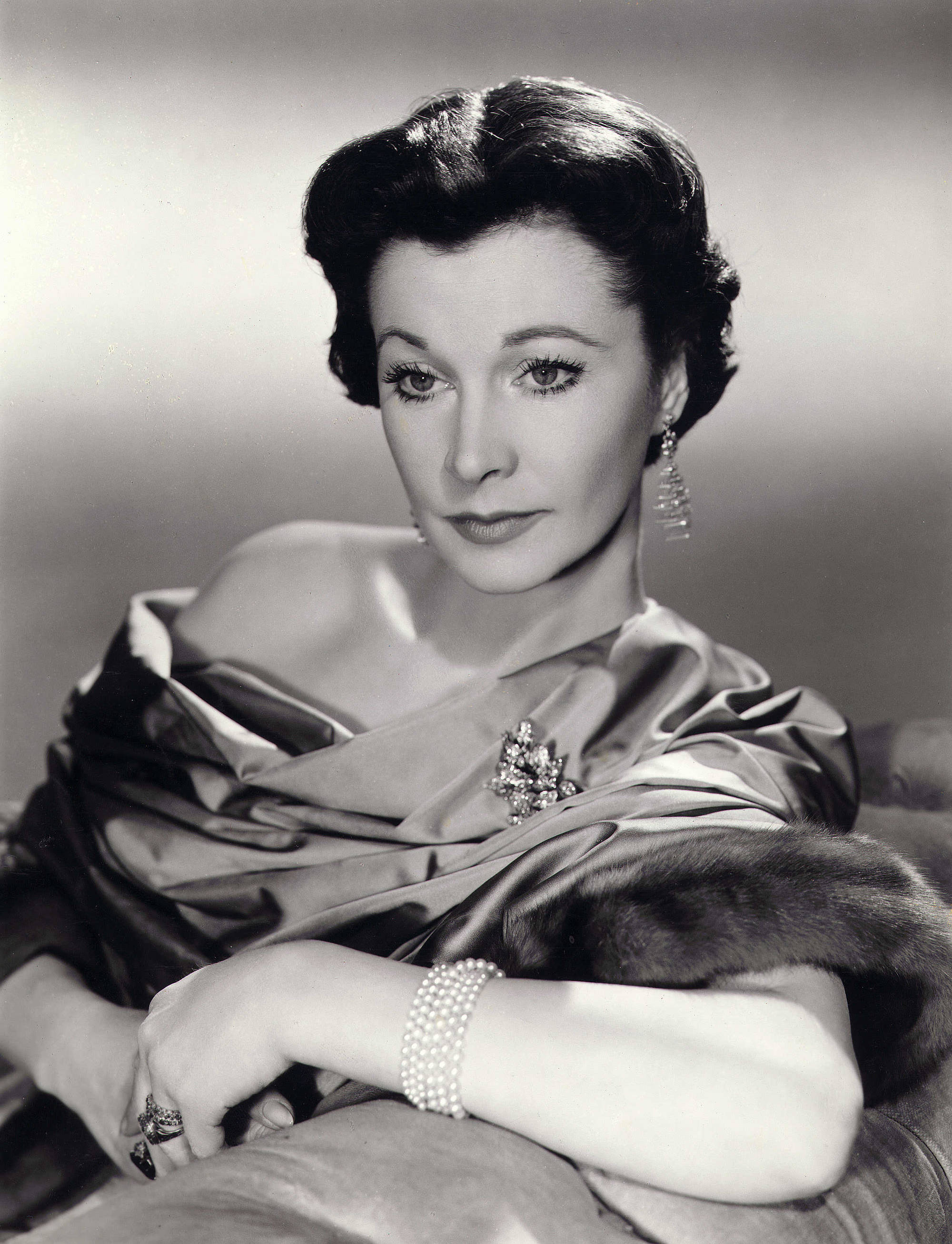 1930s hairstyles: Vivien Leigh black and white promo picture with her brown hair styled in a classic centre parted updo wearing a evening off the shoulder gown and white gloves