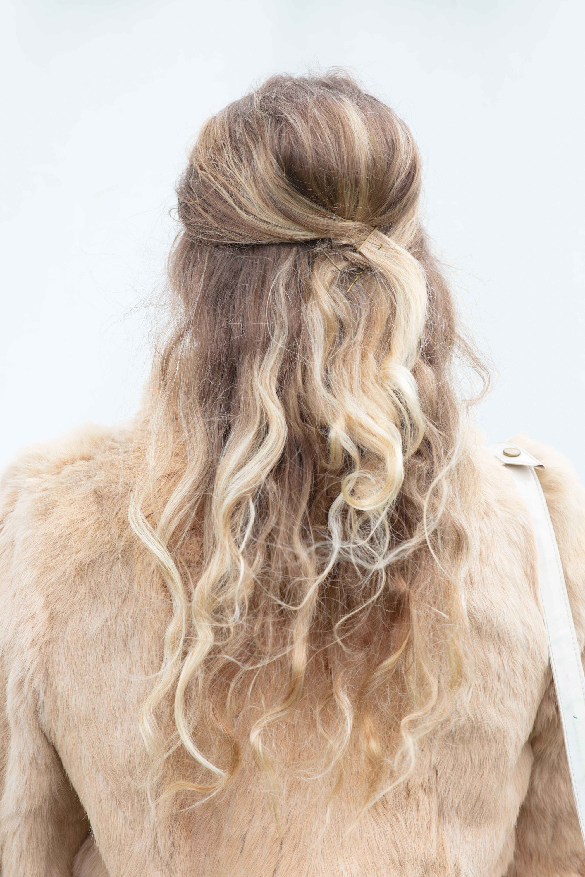 Retro hairstyles: Close up back shot of a woman with long bronde hair styled into a half-up, half-down beehive, wearing a furry jacket and posing at the Goodwood festival
