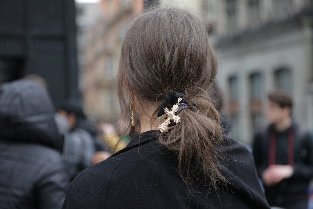 LFW hair street style: Woman with brown hair in a low messy bun wrapped with a hair chain.