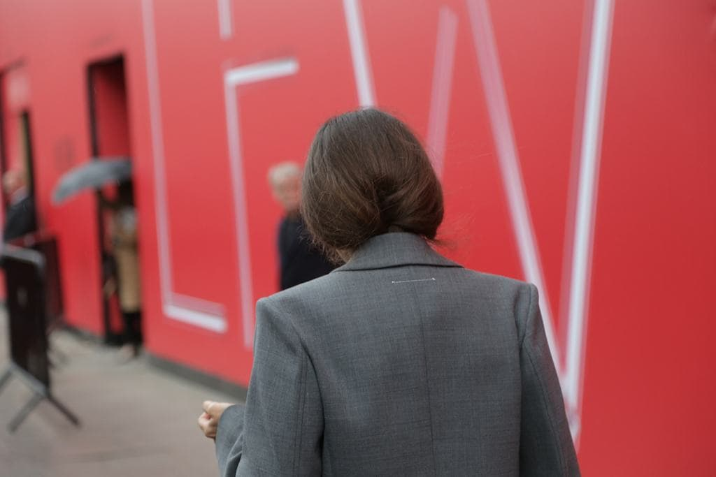LFW hair street style: Woman with brown straight hair tucked into her dark grey blazer coat.