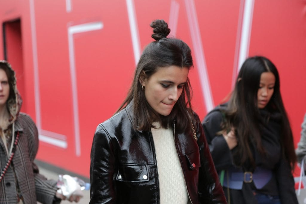 LFW hair street style: Woman with shoulder length dark brown straight hair styled in a half-up, half-down bun wearing a leather jacket.