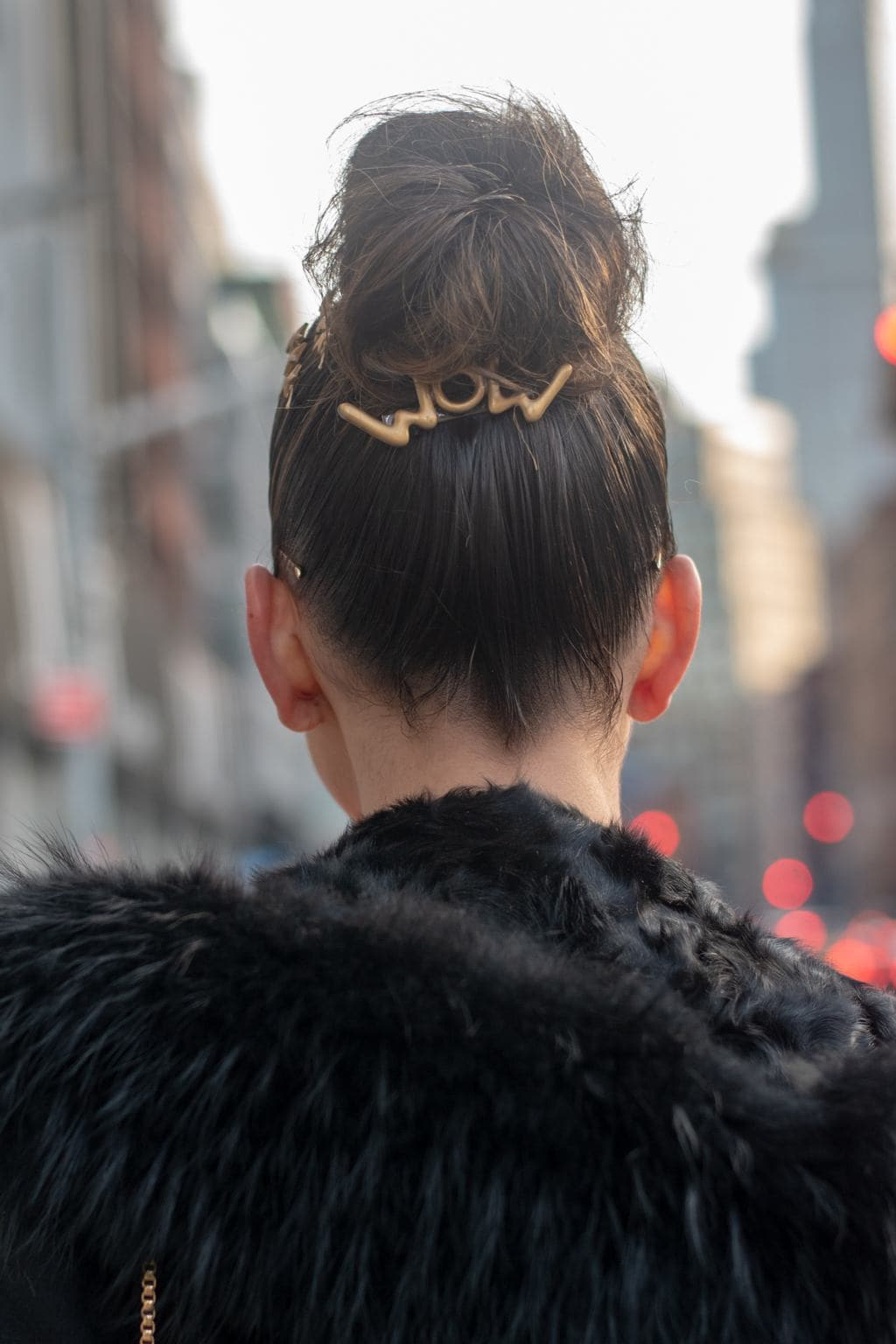 NYFW AW19 Street Style: Shot of woman with dark brown ballerina bun with wow statement slide, wearing black furry jacket