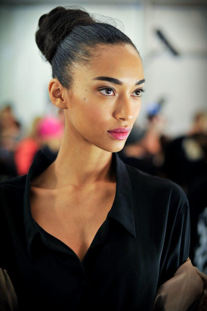 Knot bun hairstyle: Close-up backstage shot of a model with dark hair in a high slicked back ballerina bun with bun net